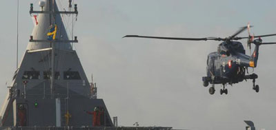 A Royal Danish Navy Super Lynx Mk 90B performs a landing on the Swedish corvette HMS VISBY