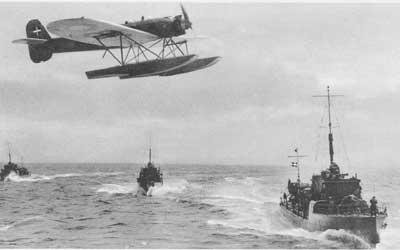 A low flying H.M. II (HEINKEL H.E.8) passing three DRAGEN Class torpedo boats